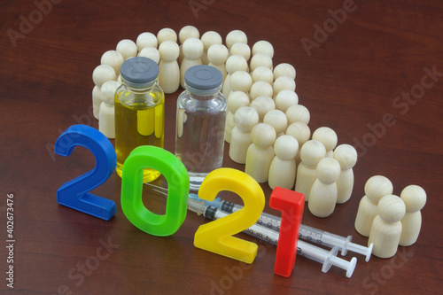 Obraz Questions about vaccination in 2021 concept. People (wooden figures) shaped as question mark, vaccine bottles, syringes and numbers 2021. - fototapety do salonu