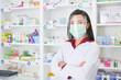 Leinwandbild Motiv Asian professional young pharmacist wearing faceshield and mask while standing at drugstore.