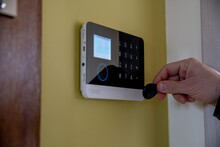 Man Unlocking And Disarming Home Security Alarm With Access Pin Card