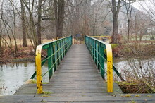 Narrow Footbridge Over A River In A Forest With Green And Yellow Rails And A Sign Post Visible At The End