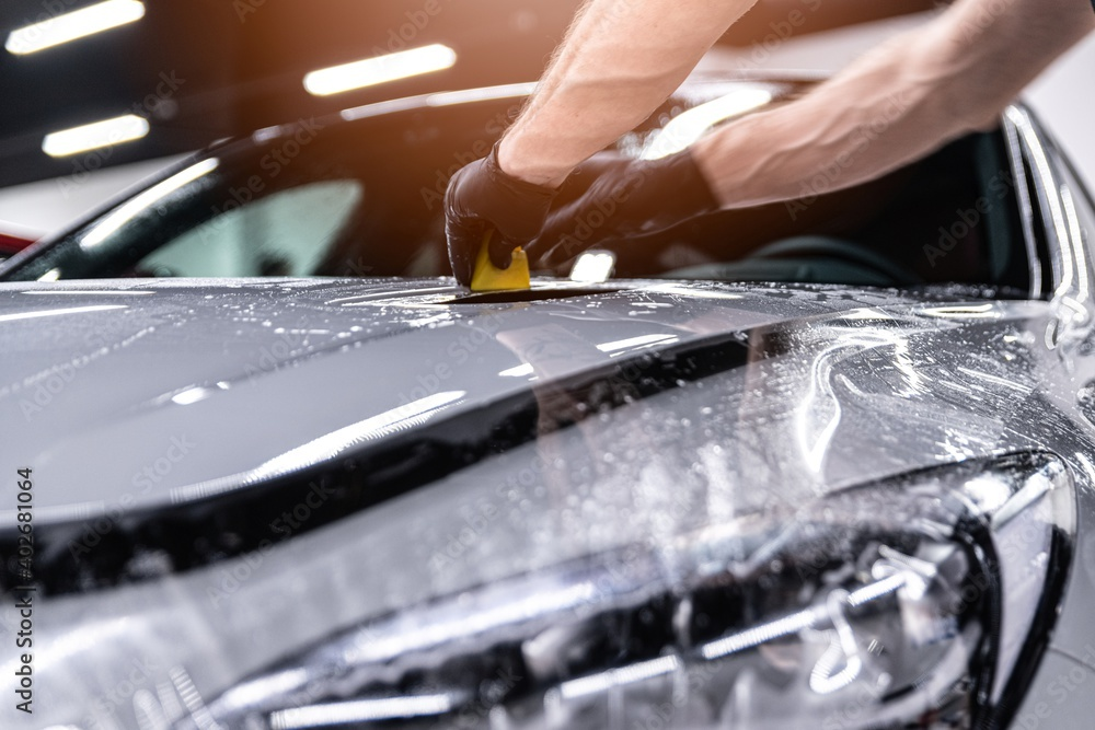 Fototapeta Car detailing studio worker applying protective ppf foil film on car body and lamps