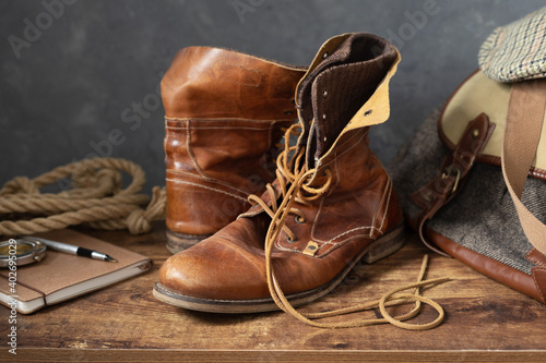 Obraz na plátne old leather travel vintage boots shoes and bag at  table