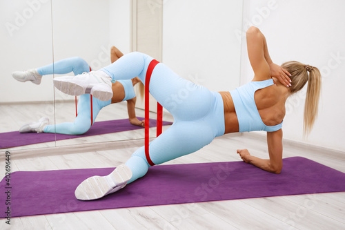 Fotografie, Tablou Fitness woman doing exercise for glutes with resistance band, clamshell