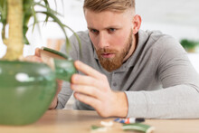 Man Repairing Flower Pot With Glue