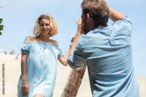 Fototapeta photographer doing fashion shoot on a sand dune