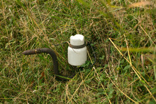 An Old Ceramic Insulator Abandoned In The Grass