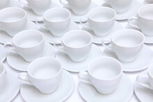 A Large Number Of White Porcelain Or Ceramic Tea Pairs On The Table. Catering Or Banquet Concept. View From Above.