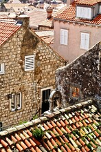 Bell On An Aging Red-tiled Roof In Old Town Dubrovnik, Croatia A City On The Adriatic Sea In Southern Croatia. It's A Prominent Tourist Destinations In The Mediterranean And UNESCO World Heritage Site