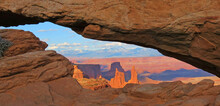 Canyonlands National Park - A View Through A Natural Rock Arch At Sunset Showing An Area Of Towering Rock Pinnacles
