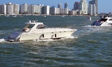 High-end Cabin Cruiser On Biscayne Bay Against A Background Of Tall Condo And Apartment Rental Buildings Overlooking The Bay.