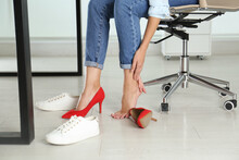 Woman Changing Shoes In Office, Closeup. Tired Feet After Wearing High Heels