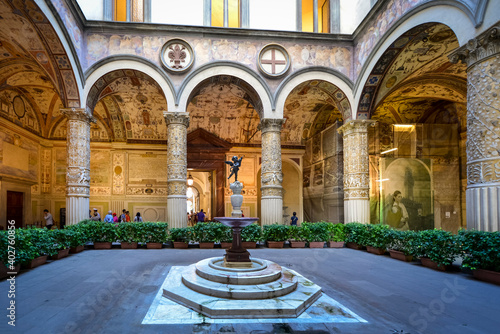 The first courtyard of the Palazzo Vecchio in Florence Italy with a small fountain with statue, frescoes on the wall and vaulted columns Fotobehang