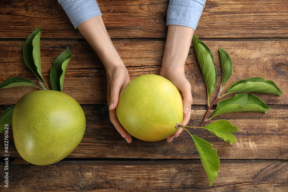 Fototapeta Woman holding fresh ripe pomelo at wooden table, top view