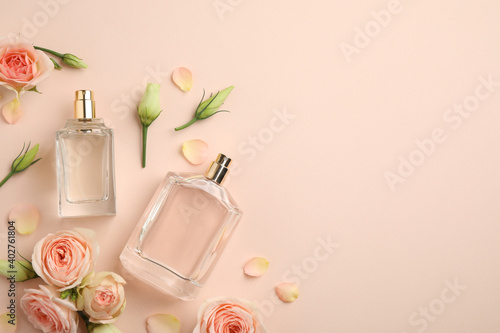 Flat lay composition with different perfume bottles and fresh flowers on beige background, space for text