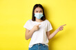 Leinwandbild Motiv Covid-19, pandemic and social distancing concept. Disappointed asian girl in medical mask, frowning upset and pointing fingers right at logo, standing over yellow background