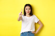Leinwandbild Motiv Confident and serious woman tell no, showing extended finger to stop and prohibit something bad, frowning and looking at camera self-assured, standing over yellow background