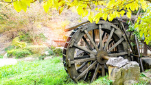 Old Waterwheel In The River In Mountain On Autumn Day.