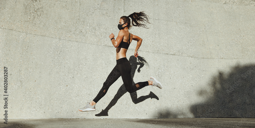 Fototapeta Fit woman sprinting outdoors
