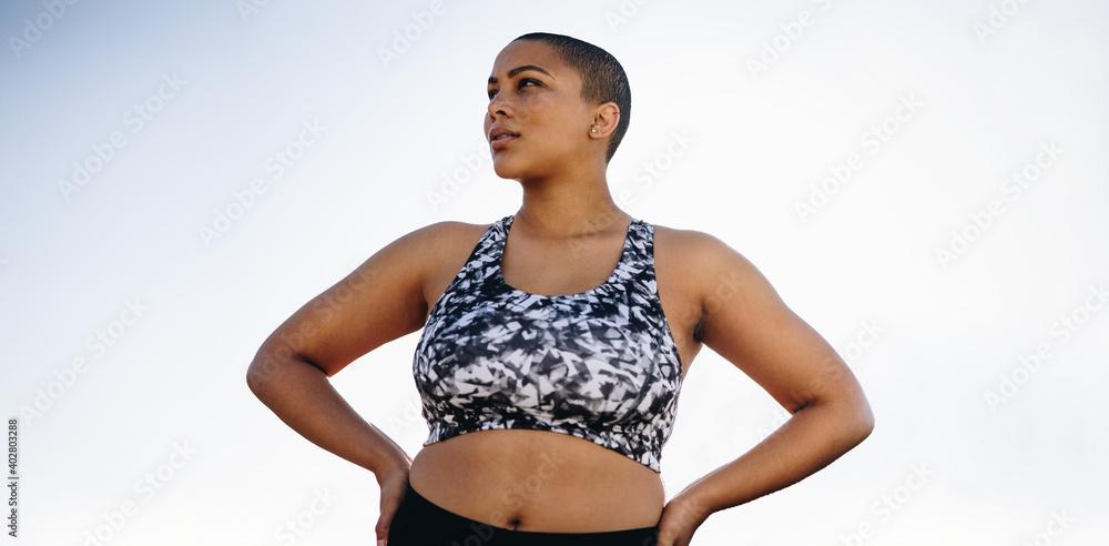 Fototapeta Curvy woman in sportswear with hands on hips