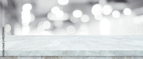 Fototapeta Empty white table top, counter, desk over blur perspective store with bokeh light background, White marble stone table, shelf and blurred shop for food, product display mockup, template banner obraz