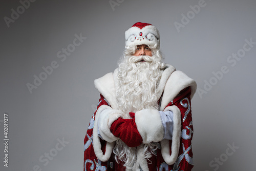 Fototapeta Portrait of emotionless Father Frost with long white beard wearing traditional costume holding hands together and looking at camera with calmness