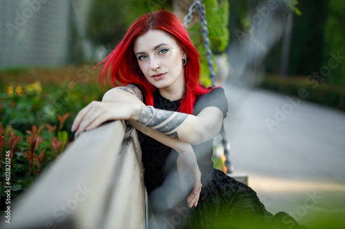 Photo red haired girl in dress walks in park