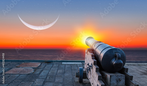 Fotografering Ramadan Concept - Ramadan kareem cannon with crescent moon at amazing sunset