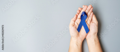 Foto March Colorectal Cancer Awareness month, Man holding dark Blue Ribbon for supporting people living and illness