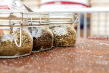 Jars With Three Different Types Of Tea Are On The Table, Alternative Medicine And Natural Food. Tea In Dry Form, For Brewing, Is Stored In Glass Jars. Street Market