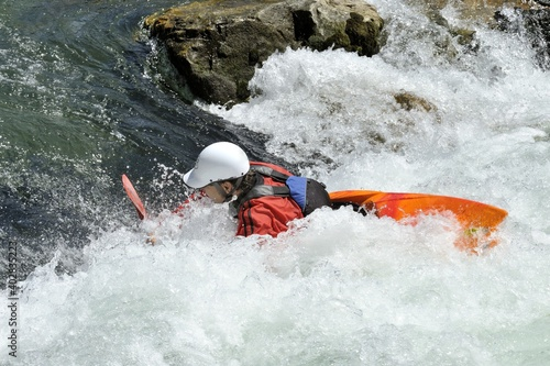 Photo athlete does stunts with canoe on the river for extreme sport
