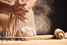 Female Baker Hands Making Dough For Bread With An Apron. Roller And Chopping Board Visible In The Background. Natural Homemade Ingredients. Dark Background, Brown Color Grading.