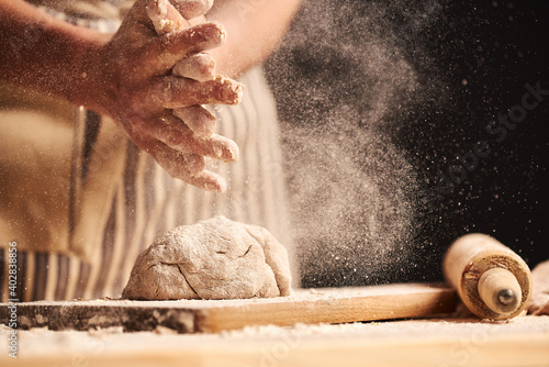 Fotografia, Obraz Female baker hands making dough for bread with an apron