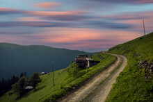Dirt Road Green Landscape And Wooden House