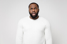 Concerned Worried Shocked Dissatisfied Young African American Man 20s Wearing Casual Basic Sweater Standing Keeping Mouth Open Looking Camera Isolated On White Color Wall Background Studio Portrait.