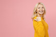 Side view of funny elderly gray-haired blonde woman lady 40s 50s years old in yellow casual sweater pointing thumb aside on mock up copy space isolated on pastel pink color background studio portrait.