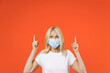 canvas print picture - Elderly gray-haired blonde woman lady 40s 50s in white basic t-shirt face mask to safe from coronavirus virus covid-19 during quarantine pointing index fingers up isolated on orange background studio.