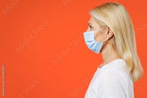Side view of elderly gray-haired blonde woman lady 40s 50s in white t-shirt sterile face mask to safe from coronavirus virus covid-19 during quarantine isolated on orange background studio portrait.