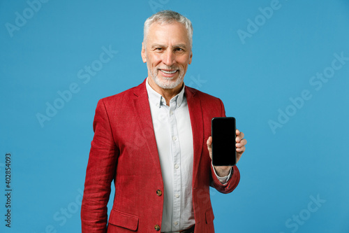 Smiling handsome elderly gray-haired mustache bearded business man wearing red jacket suit standing hold mobile cell phone with blank empty screen isolated on blue color background studio portrait.