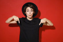 Shocked Amazed Young Brunette Woman 20s Years Old In Casual Basic Black T-shirt Hat Standing Point Index Fingers Down On Mock Up Copy Space Isolated On Bright Red Color Background Studio Portrait.
