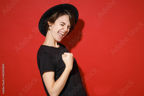 Side view of happy young brunette woman 20s years old wearing casual black t-shirt hat doing winner gesture celebrating clenching fists say yes isolated on bright red color background studio portrait.