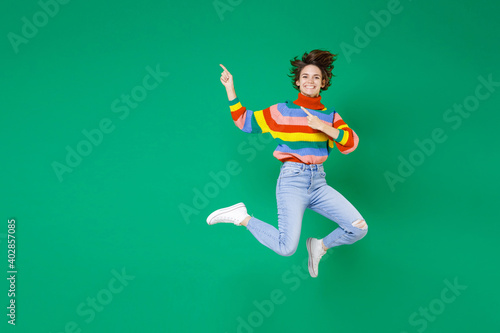 Full length of smiling laughing pretty young brunette woman 20s in colorful sweater jumping point index fingers aside on mock up copy space isolated on bright green color background studio portrait.