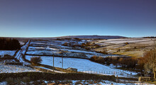 Snowy Nidderdale And Late Afternoon Sun Lights Up Moorland Pastures, Fields And A Single Track Road.