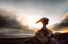 Hiker Standing On The Cliff Mountain Pointing The Sky With Finger - Successful Man On The Top Of The Hill At Sunset