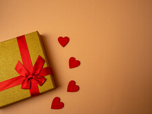 A Yellow Gift With A Ribbon In The Form Of A Butterfly Knot Lies Next To Four Red Hearts