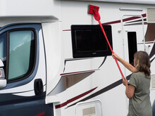 A Lady Washes And Cleans Her Motorhome Recreational Vehicle With A Red Long Handled Mop