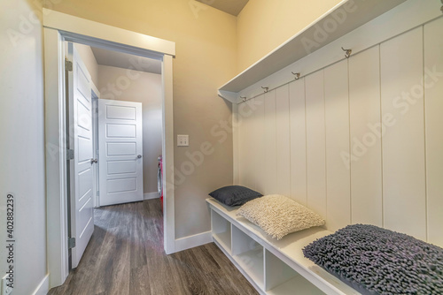 Leinwand Poster Mud room interior of a house with hooks shelves and built in bench with pillows