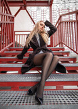 Fototapeta Na drzwi - Woman with perfect legs in pantyhose and shoes with high heels posing outdoor on the red stairs