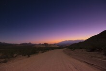 Dirt Road Into The Unknown Under A Starry Twilight Sky.