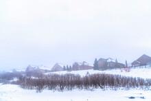 Foggy Neighborhood On A Snowed In Mountain With Houses Under Overcast Sky
