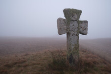 Ancient Religious Christian Cross Made Of Stone, Covered By Green Moss On A Hill Covered By Thick Mist